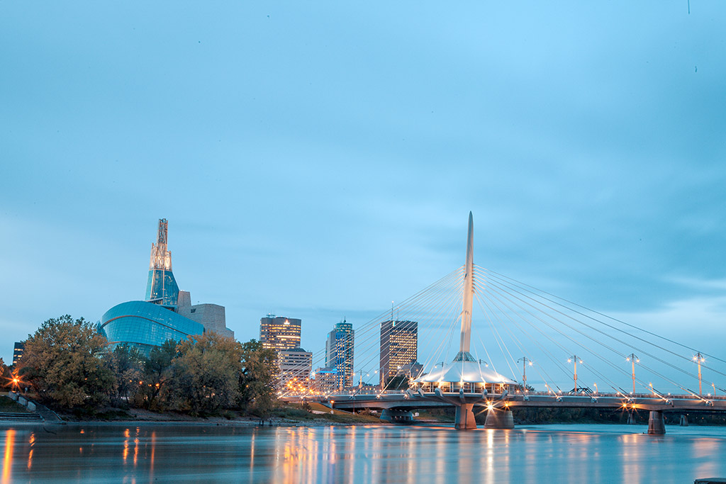 Downtown Winnipeg, with the Canadian Museum for Humans Right (left) and The Esplanade Riel pedestrian bridge. This view is from St. Boniface, a city ward founded in 1818 - home to one of the largest francophone communities west of the Great Lakes and the birthplace of Louis Riel. Photo by Kyle Thomas