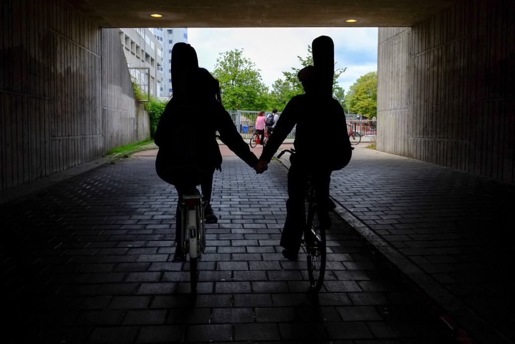 A musical couple rides hand in hand in Amsterdam. Photo by David Niddrie