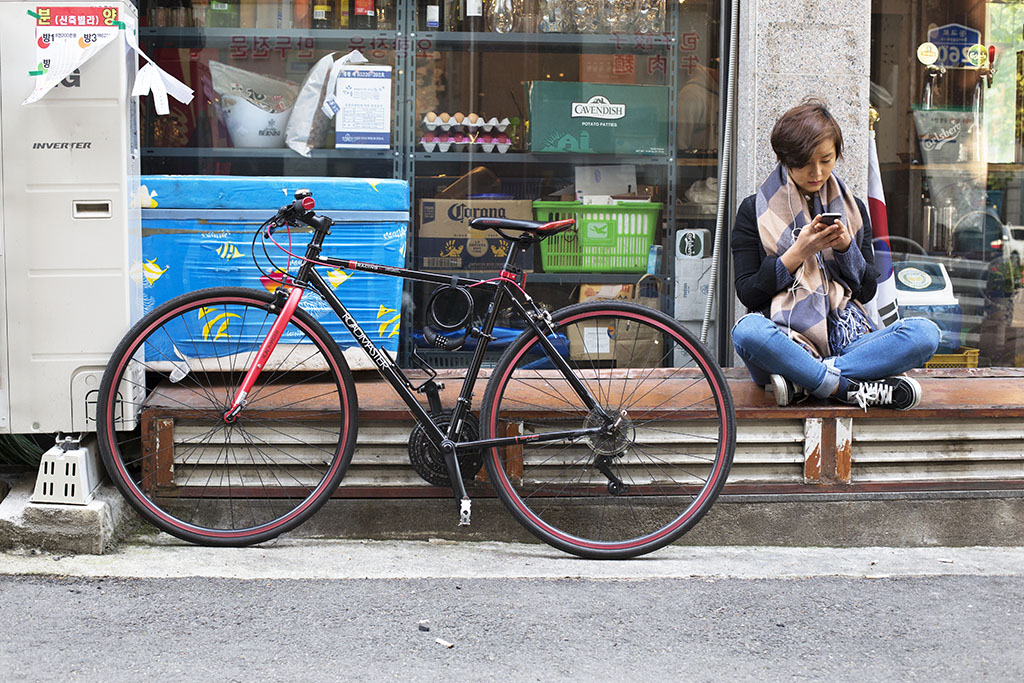 A rider relaxes outside a Seoul bar.