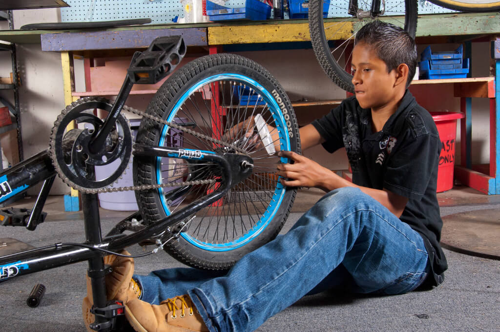 A boy works on a bike at a Trips For Kids after-school program