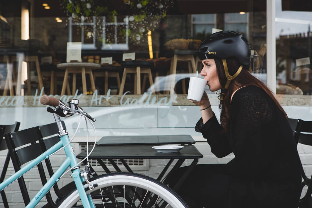 Woman wearing the Bern Melrose Helmet in Black, sipping from a cup as she rides