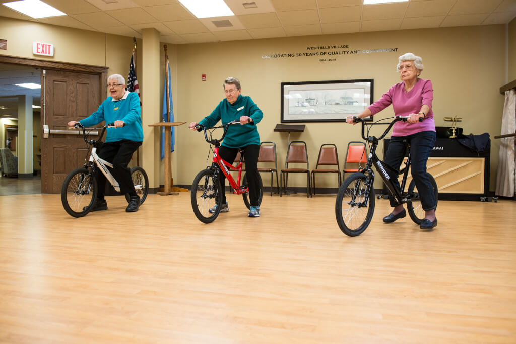 Three elderly people at a retirement home riding the STRIDER Balance Bikes