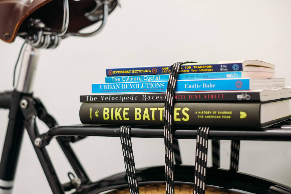 Stack of biking books on a bike rack
