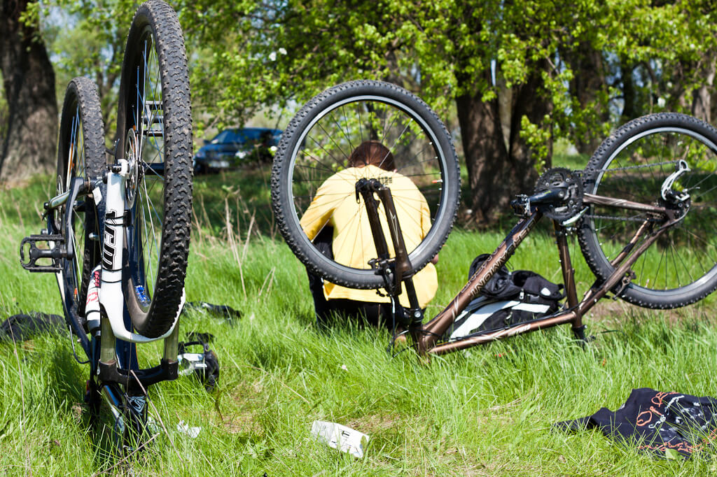 Two bike being serviced in a meadow