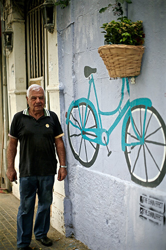 A shop owner stands behind the new painting on his wall. Photo courtesy of Zeina Hawa.